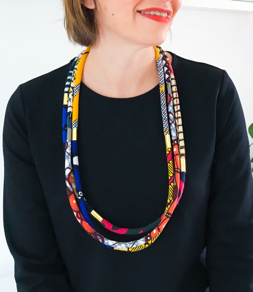 A person wearing multiple sets of rope necklaces in the longer length configuration. Pattern Punch