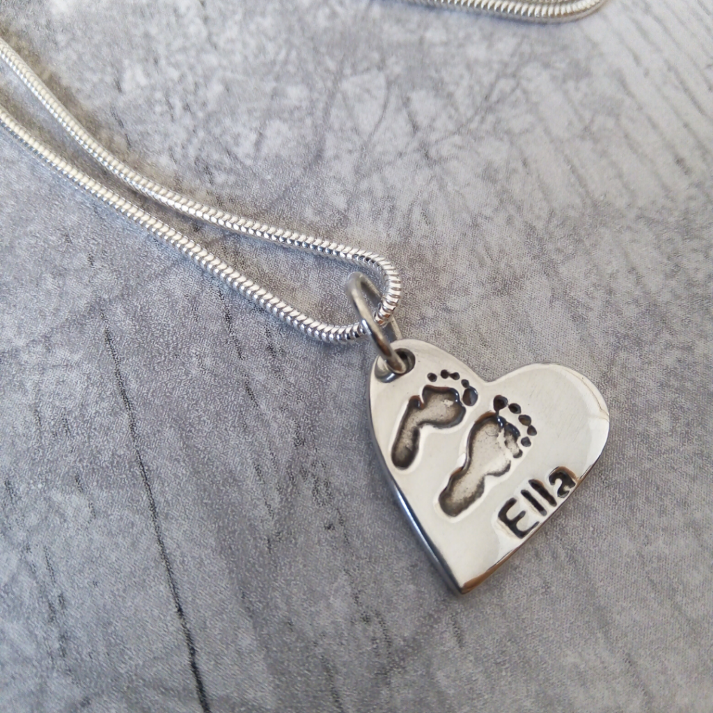 true love keepsakes, heart footprint charm necklace made from pure silver personalised with a name attached to a snake chain