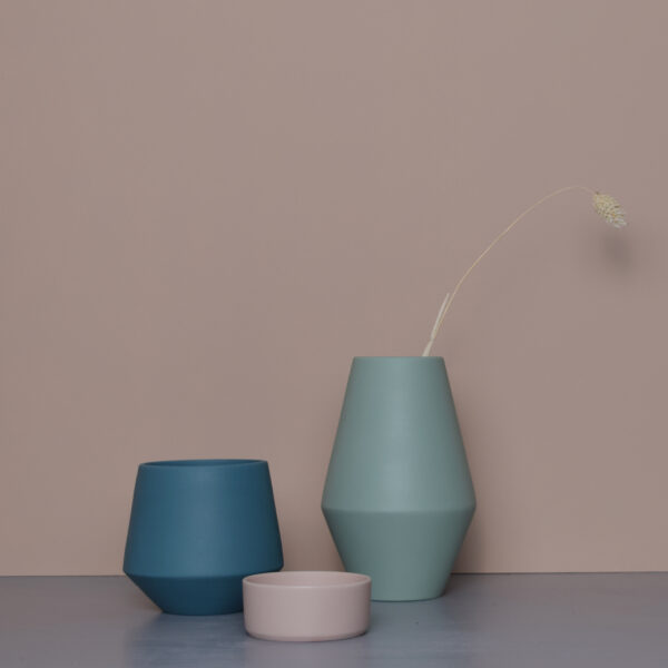 a pale pink background, in front of it is a medium size vase in a mint colour, on the right from it is a deep turquoise toned cup and at the front is the blossom tealight in subtle pale pink.