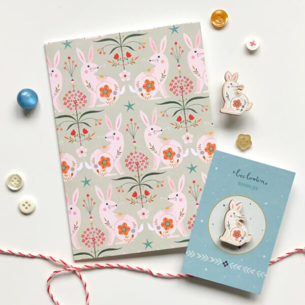 folk rabbit pattern greetings card and eco-friendly wooden pin designed by Bee Brown on a white background and surrounded by pretty little buttons and parcel string