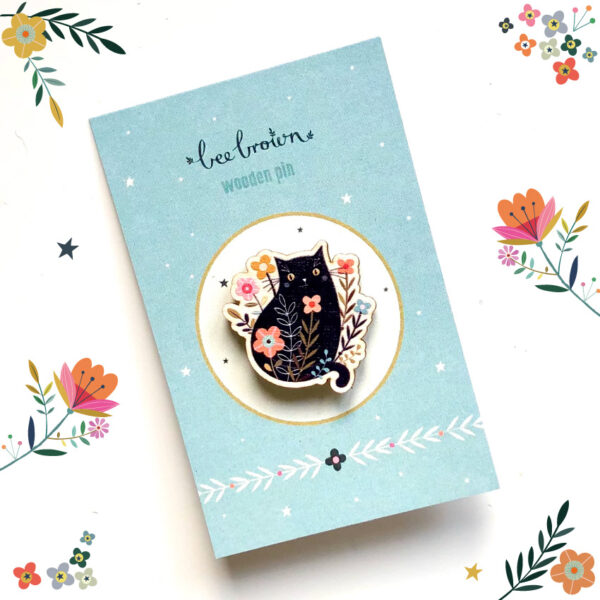 a wooden pin brooch of a garden cat sitting in flowers designed by Bee Brown Illustration made from Birch plywood on a recycled paper backing card
