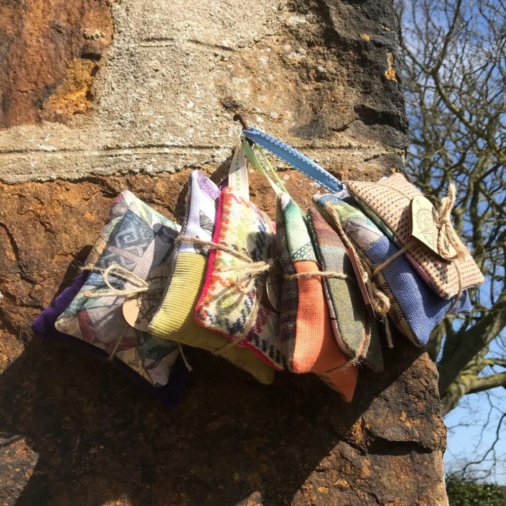 Compass Rose Studio-Lavender bags hanging on a hook against a stone wall with trees in the background