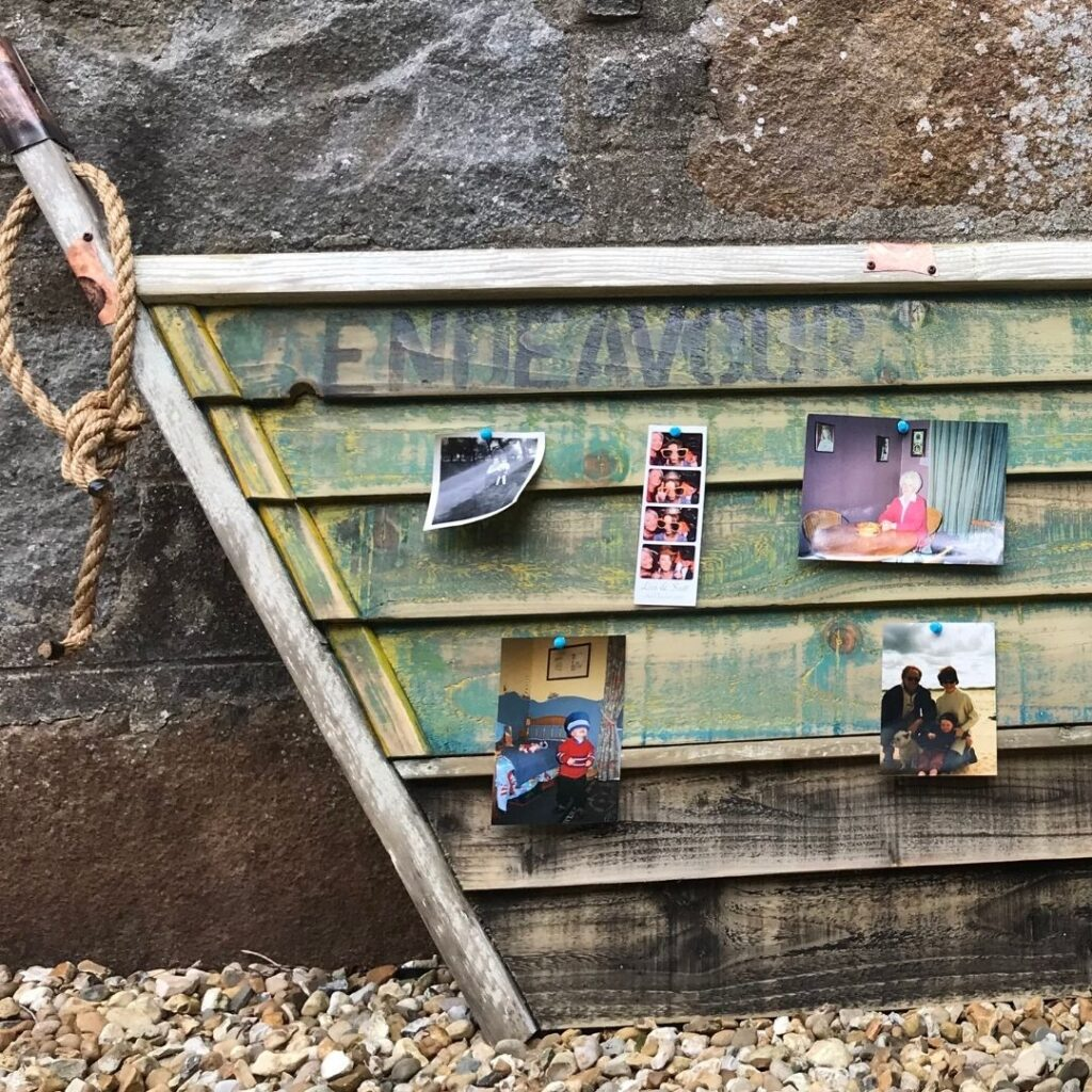 Compass Rose Studio-Recycled Wood noticeboard in the shape of a boat with photographs pinned to it.