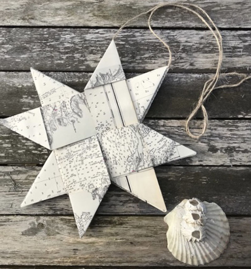 Compass Rose Studio, paper star made from old black and white nautical charts, with a string loop to hang it up. Photographed on a wooden table next to a shell