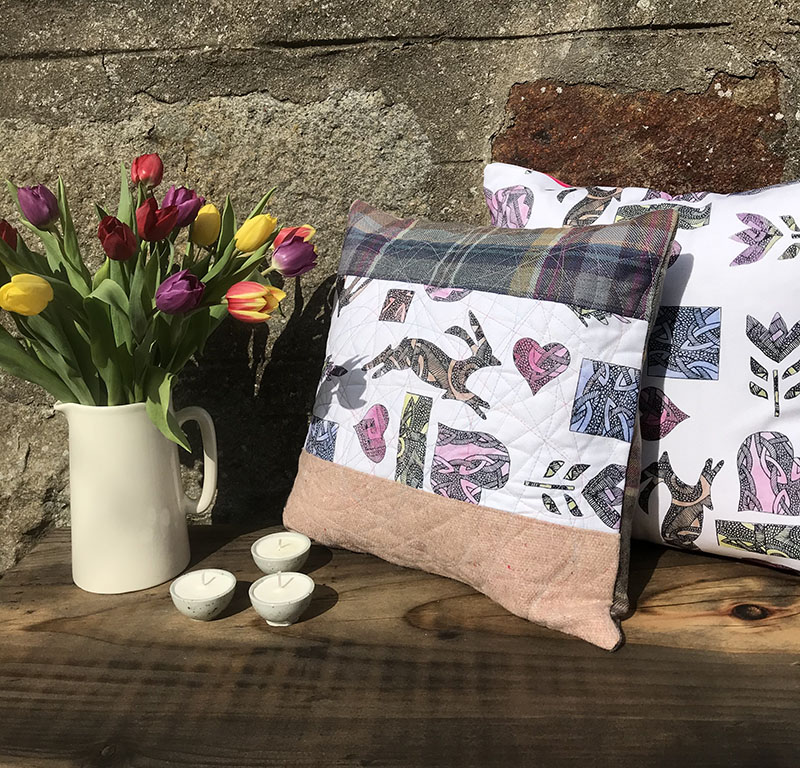 Compass Rose Studio , two cushions on a wooden bench against a stone wall with a vase of tulips. One is a mixture of printed fabric an tweed , the other is a bold pastel print both with hares and hearts.