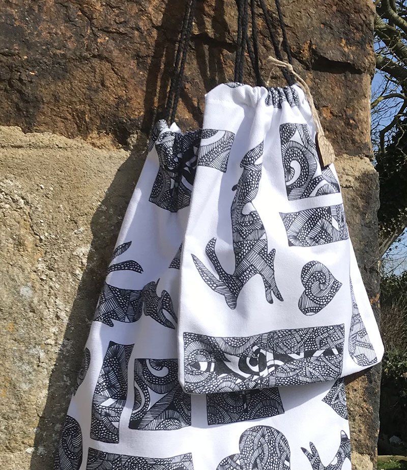 Compass Rose Studio, two black and white print drawstring bags , against a stone wall with trees in the background