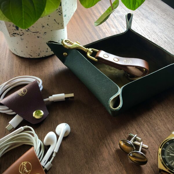 Paulo Vulpes atelier olive green leather valet tray On mid century table, leather cable and headphone organiser and London tan brass keyring