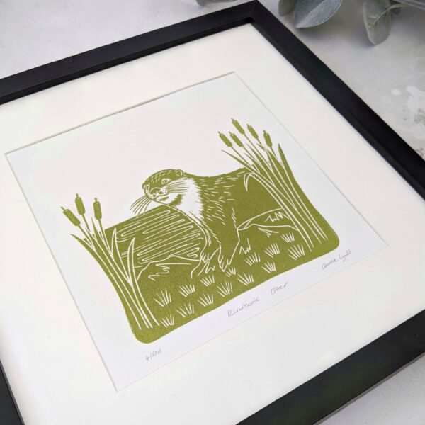 A linocut print of an otter on a riverbank framed by bulrushes in green - rose and hen