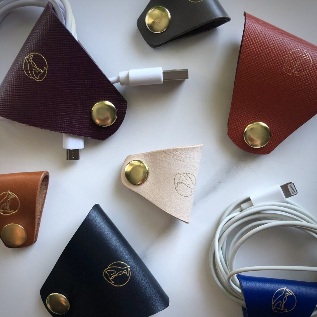 Paulo Vulpes atelier small and large leather cable keeper, natural navy orange forest cobalt leather cable tidy with brass snap fastener with iPhone accessories on white background