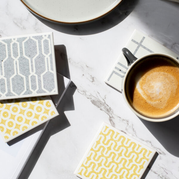 Tile coasters in grey and yellow geometric designs by Yellow Room Designs