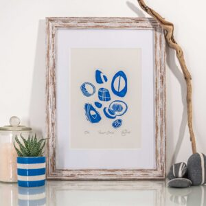 Hannah Cantellow Studio Printmaker Pocket Stones Blue Pebbles Linocut Print Framed with bath salts in a jar, blue and white cornishware cup with succulent plant and driftwood