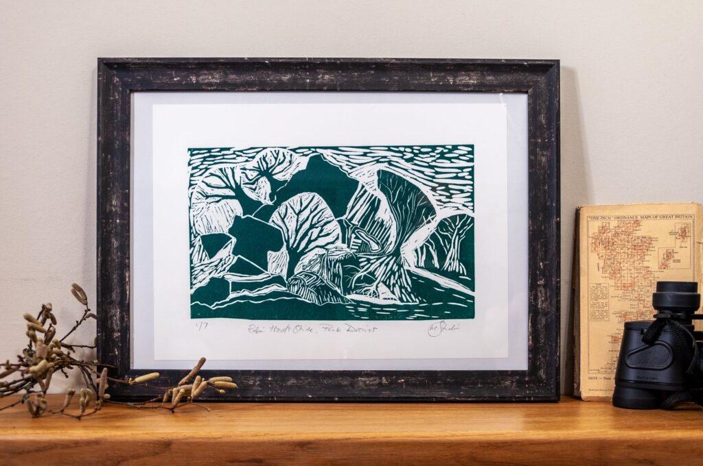 Hannah Cantellow Studio Robin Hood's Stride Peak District Green Linocut Tree Print with binoculars and map on wooden shelf