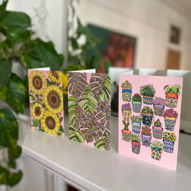 Three card designs, sunflowers, tropical leaves and pot plants, lined up next to each other on fireplace with plant and mirror in background