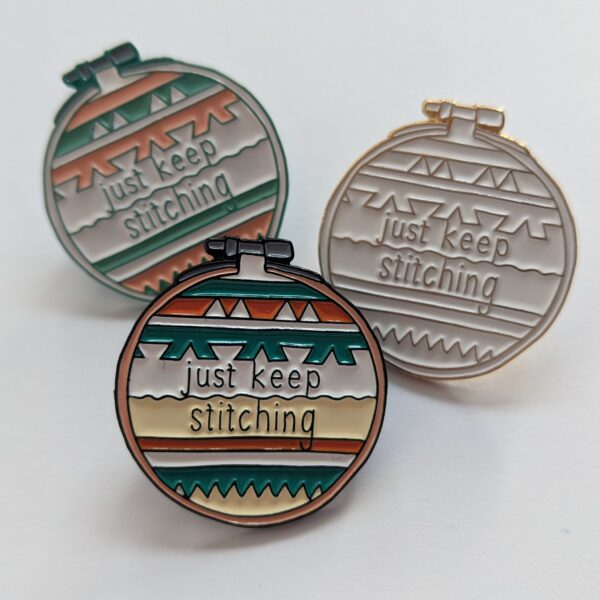 Little Light Stitchery enamel pins. three pins each with the quote just keep stitching on a stripy geometric background. Bright, pastel and white gold colourways