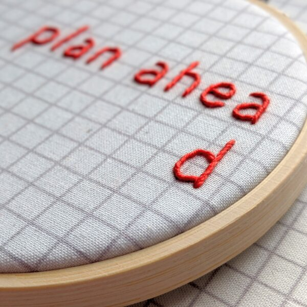 Little Light Stitchery Plan ahead hoop. Hand embroidered plan ahead quote on a grey grid fabric