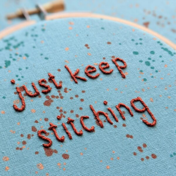 Little Light Stitchery just keep stitching hoop. A hand embroidered quote reading just keep stitching on a speckled aqua fabric