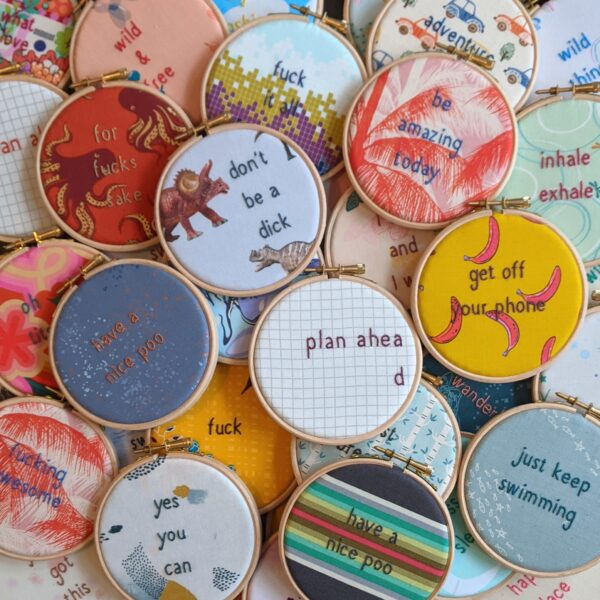 Little light stitchery pile of quote hoops. Lots of different hand embroidered quote hoops on colourful and patterned fabric