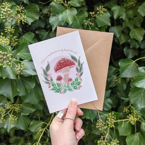 Mushroom Greetings Card being held against a green bush background