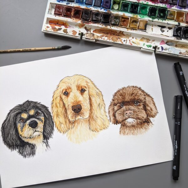Trio of Custom Watercolour Dogs Painting, surrounded by Watercolour paint palette, paintbrush and pens