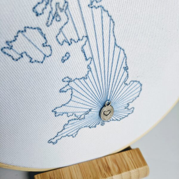 Little Light Stitchery Starburst Map. A hand embroidered country outline with a heart over a specific city with a heart charm attached. Starbursts come out from the city