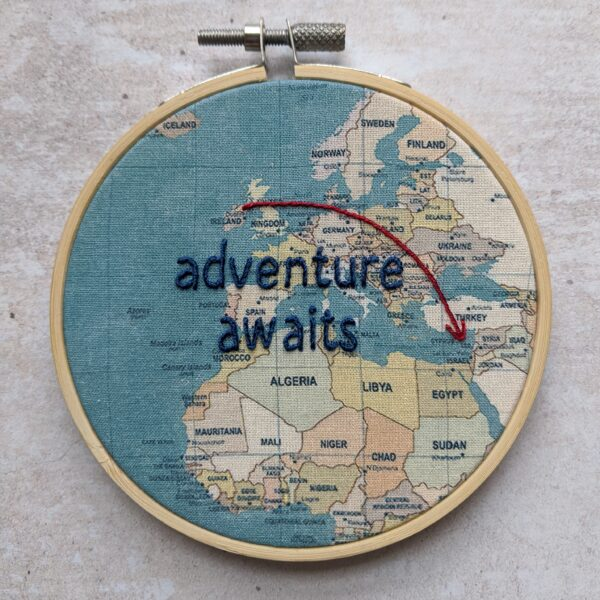 Little Light Stitchery Travel journal hoop. World map fabric with a line and arrow linking two countires and the hand embroidered words adventure awaits