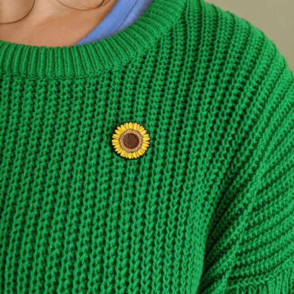 Yellow Sunflower enamel pin being worn on bright green knitted jumper