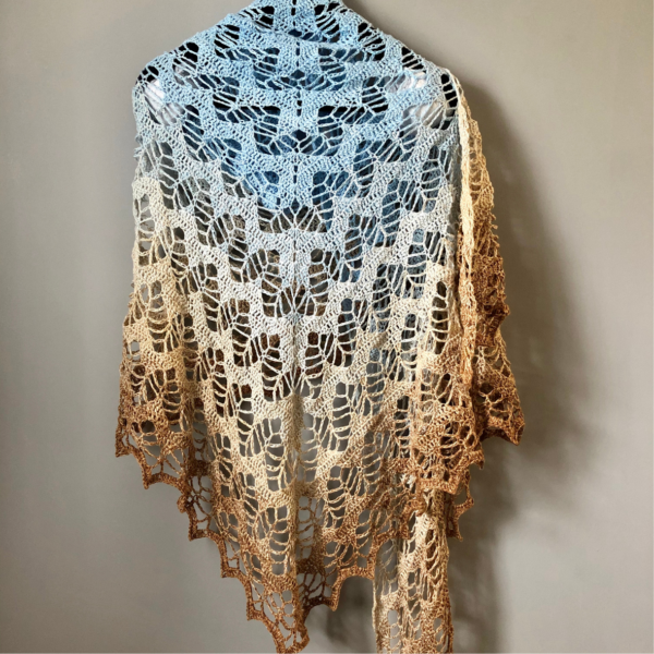 A crochet shawl in blue, cream and coffee colours