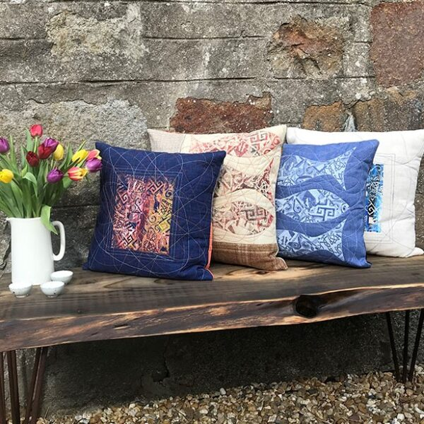 Compass Rose Studio- Four Cushions on a wooden bench against a stone wall with a jug filled with tulips
