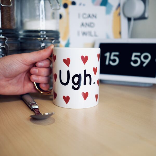 Showcasing a white mug with a love heart repeat pattern