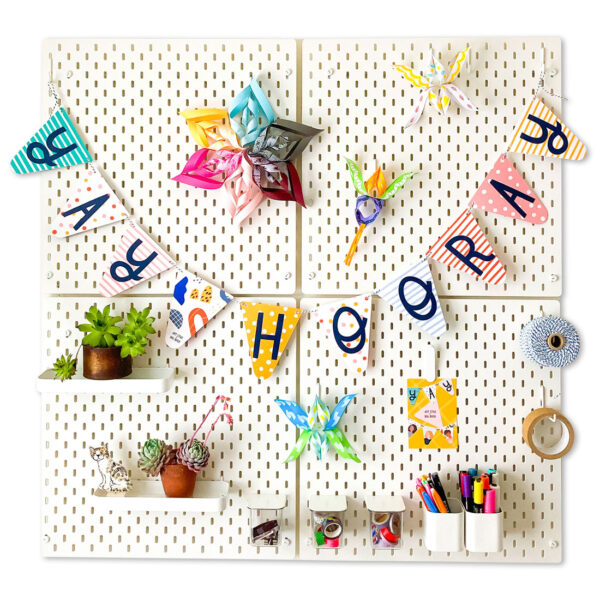 Art Star Paper Party Bunting with the words Yay Hooray, hanging on white pegboard with assorted colourful paper decorations, houseplants and stationery items
