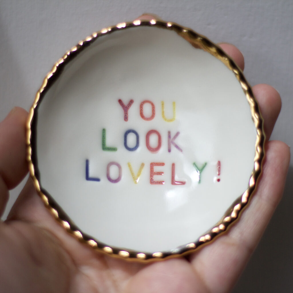 Helen Manterfield a small ceramic bowl with gold scalloped edges and the message 'you look lovely' stamped and painted in a rainbow pattern