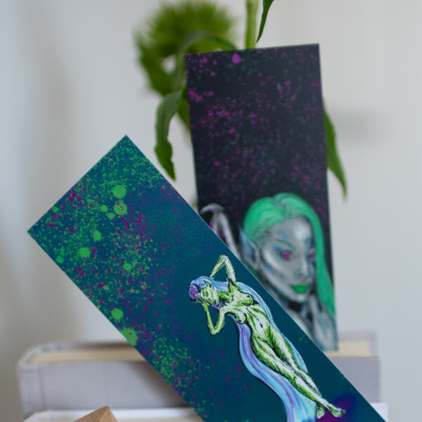 Diva Collection Bookmarks by Hannah Kate Makes. Two bookmarks poking out the top of books on a shelf. One showing the green Drama Queen illustration, the other a green haired dark angel.