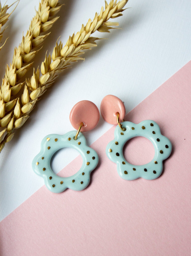 Blue flower shapes attached to pink circles. Earrings by Helen Manterfield.