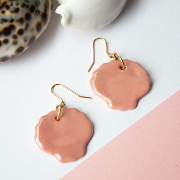 Two pink earrings with mother of pearl lustre attached to gold-plated hooks, by Helen Manterfield