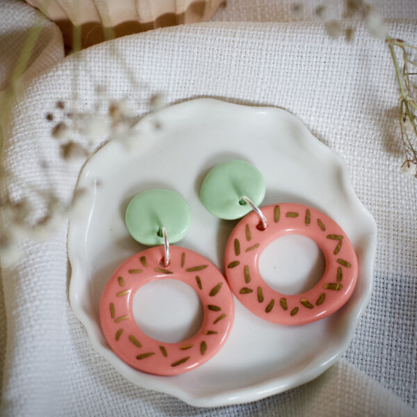 Helen Manterfield porcelain earrings coral pink hoops attached to light green circles decorated with gold lustre sprinkles