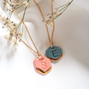 One pink and one blue hexagon pendants on gold chains by Helen Manterfield