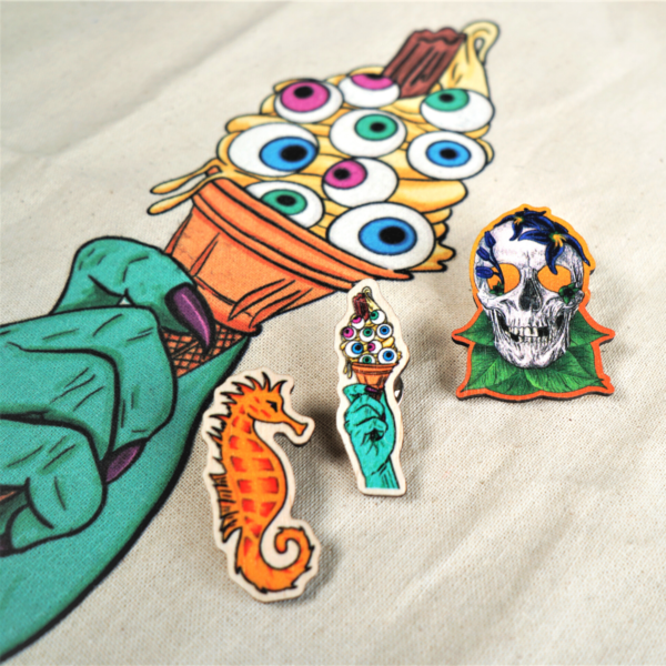 Wooden Pins by Hannah Kate Makes. Three wooden pins are shown. One orange seahorse called George. One green witchy hand holding an ice cream topped with eye balls, called Eye Scream. One skull adorned with deadly nightshade, called Bella Donna Kiss.