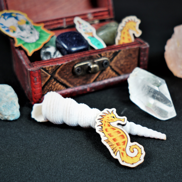 Wooden Pins by Hannah Kate Makes. Three wooden pins are shown displayed in a miniature treasure chest. One orange seahorse called George. One green witchy hand holding an ice cream topped with eye balls, called Eye Scream. One skull adorned with deadly nightshade, called Bella Donna Kiss.