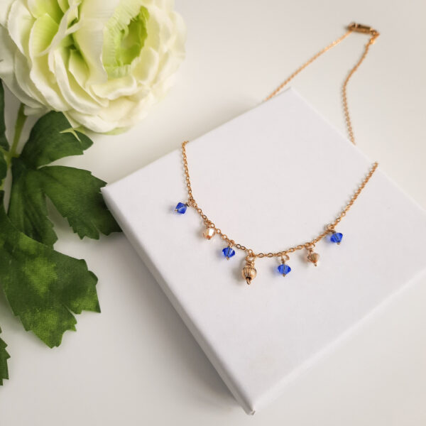 Watermeadow Lane Jewellery, Golden Sapphire Drop necklace made of 14k filled gold with sapphire blue and gold crystals and golden bead attached to the chain.