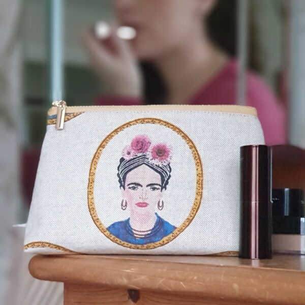 lifestyle photo of a polished metal zip bag in a natural fabric with a stylized portrait of Frida Kahlo printed on the fabric