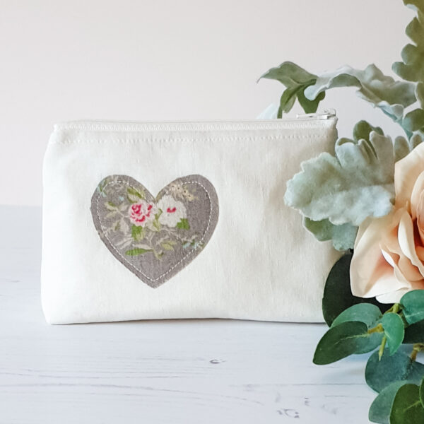 Box bottomed zip bag in ivory linen featuring a floral applique heart in natural beige ground and pink & white roses