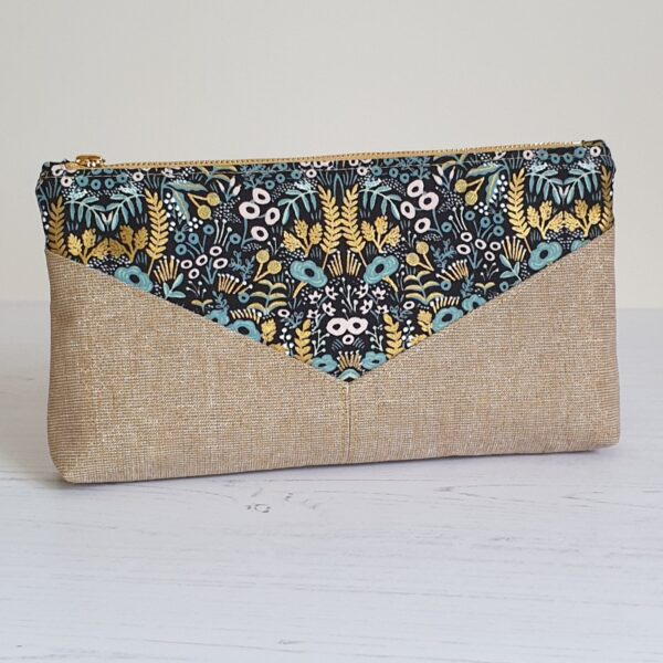 Oblong clutch bag detailing a V shape in Rifle Paper floral black green and gold fabric and a metallic gold fabric beneath the V finished with a polished gold zip