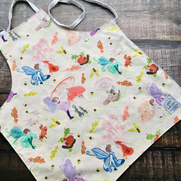 Faith Zuber vintage print showing fairies and woodland creatures on a child's apron