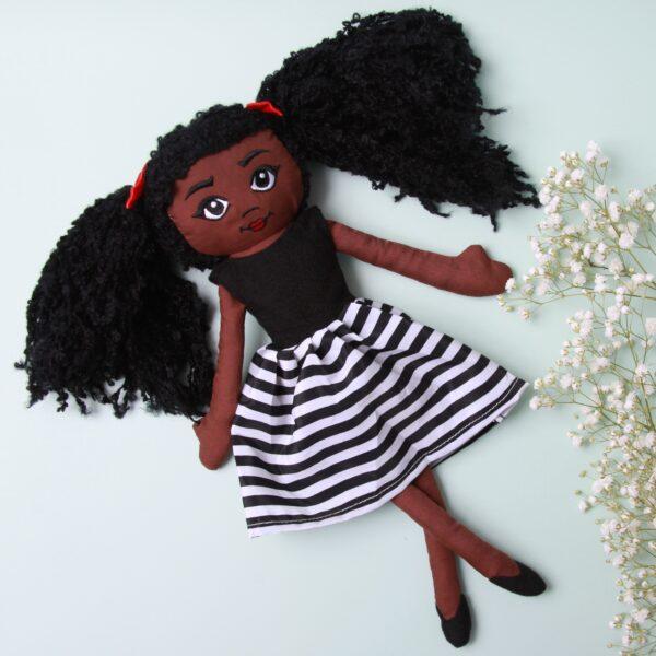 Amaris and chaya A black girl fabric doll wearing a white and black stripe dress