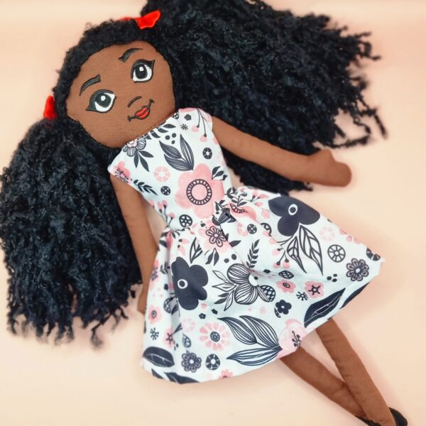 Amaris and chaya A black girl fabric doll wearing a pink and black dress