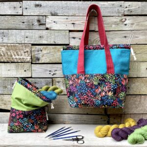 A green project pouch sits next to a hanging teal On The Go bag. Both bags have a floral base which has a black background with bright flowers