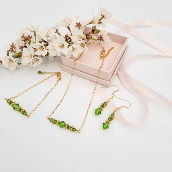 Watermeadow Lane Jewellery three pieces of jewellery consisting of necklace, bracelet and drop earrings, all in gold beads and green crystals to create a bar necklace and bracelet and straight drop earrings.