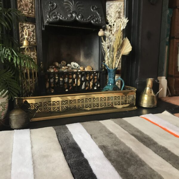 A view of a striped sheepskin rug in front of a fireplace.