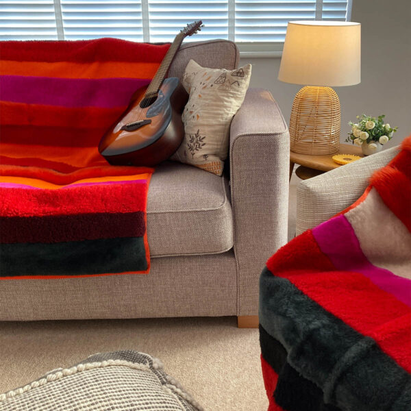 A view of two boldly striped deadstock sheepskin rug in reds, oranges and pinks, used as throws upon a sofa and armchair.