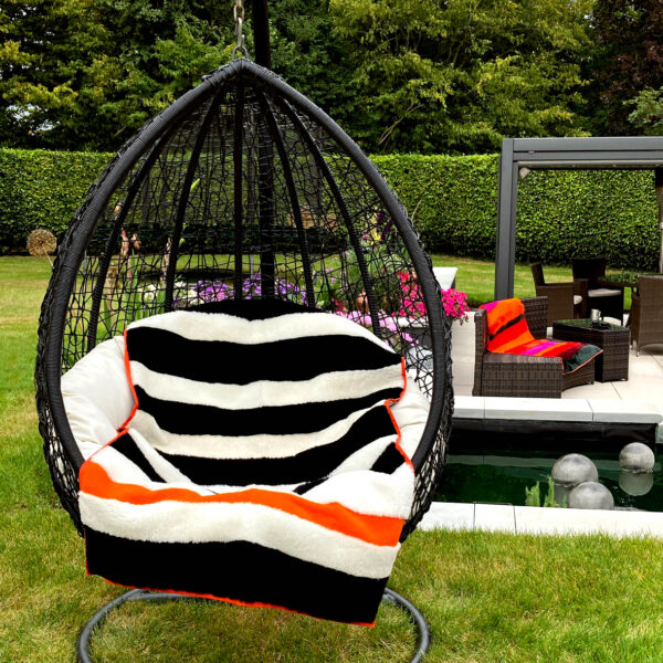 A view of two boldly striped deadstock sheepskin rug in black + white, used as a throw on a garden swing chair.